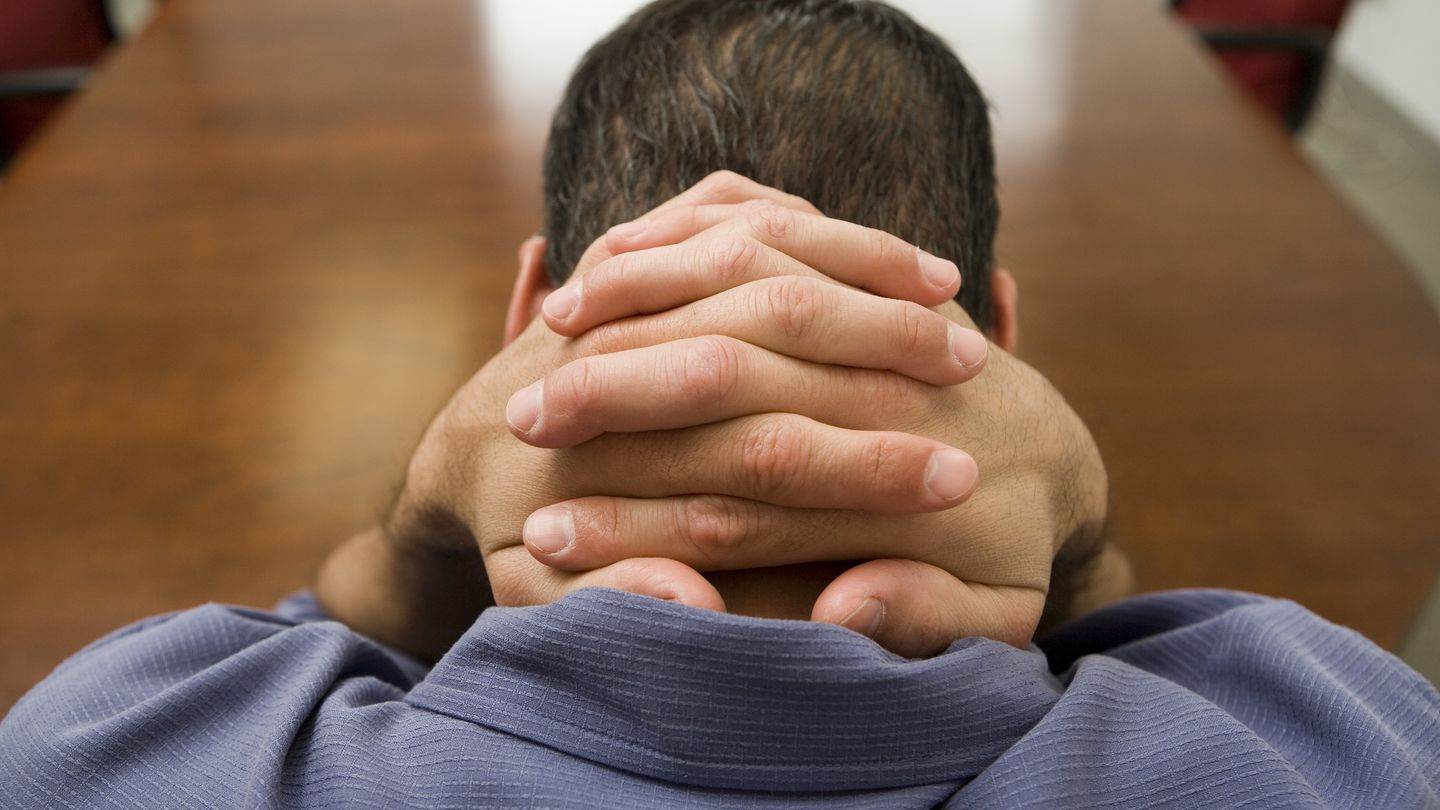 Stressed man with hands behind his head --- Image by © Bill Varie/Somos Images/Corbis