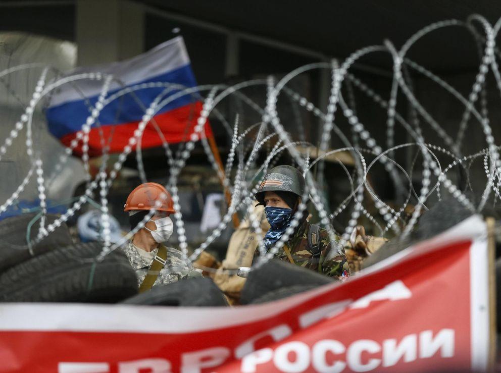 Dos prorrusos tras la barricada que protege el edificio tomado en Donétsk (Reuters).