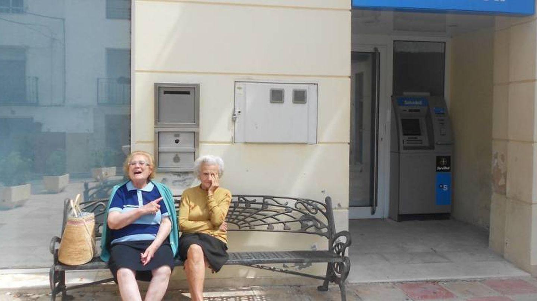 Dos jubiladas, sentadas a las puertas de una oficina cerrada. (V. R.)