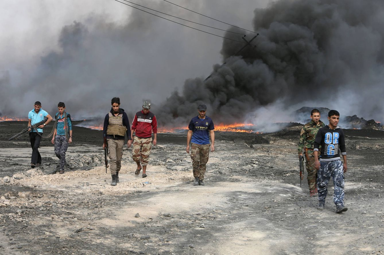 Foto: Combatientes tribales caminan entre pozos de petróleo incendiados por el ISIS tras su expulsión de Qayyara (Reuters).