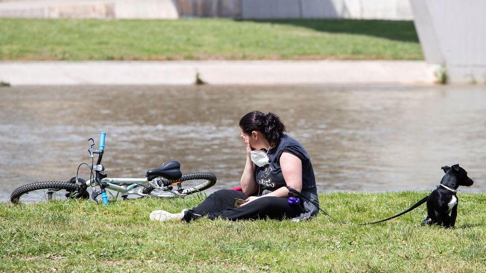Foto: Una mujer y su perro descansan en el parque fluvial del Besós. (Efe)