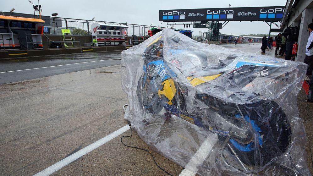 Foto: Una moto en el paddock de Silverstone, tapada por un plástico por la lluvia. (EFE)