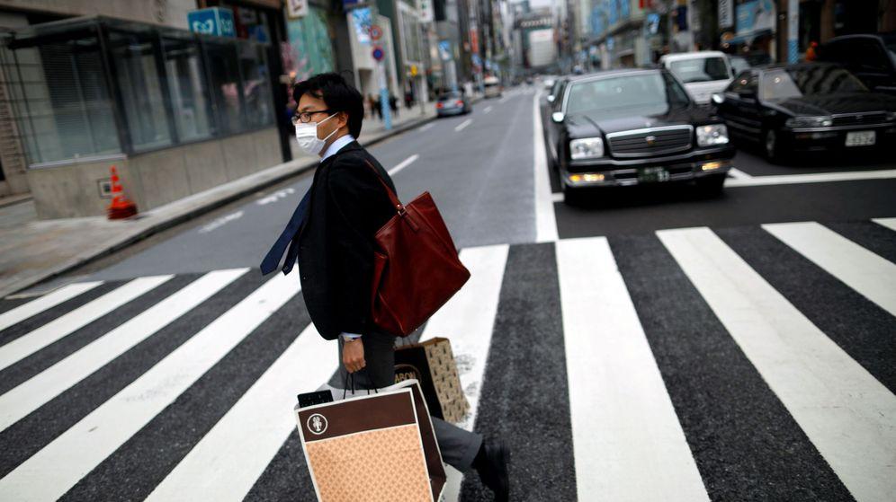 Foto: Un hombre con mascarilla pasea por las calles de Tokio, en el distrito de Ginza. (Reuters)