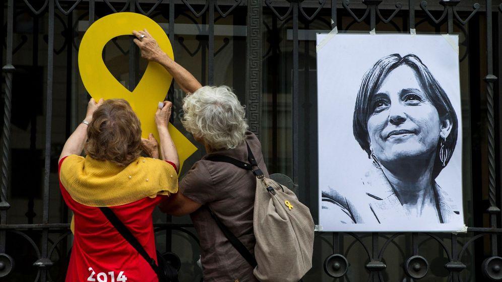 Foto: Dos mujeres cuelgan un lazo amarillo durante el acto de la campaña Free Forcadell en Sabadell. (EFE)