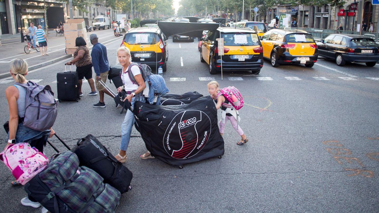 Unos turistas llevan sus maletas mientras los taxistas de Barcelona mantienen las concentraciones en el centro de la ciudad. (EFE/Quique García)