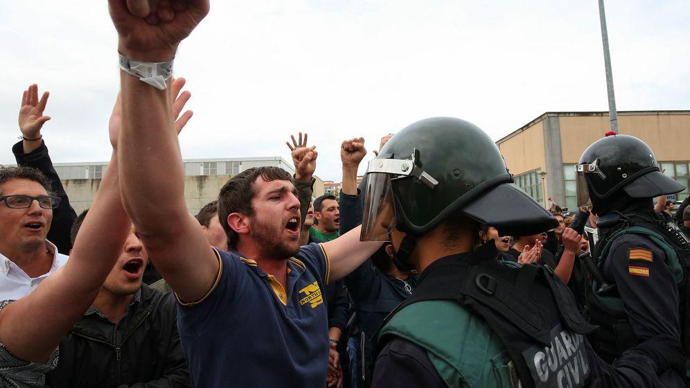 Foto: Un independentista se encara a un agente de la Guardia Civil cerca de un centro electoral el 1 de octubre (EFE)