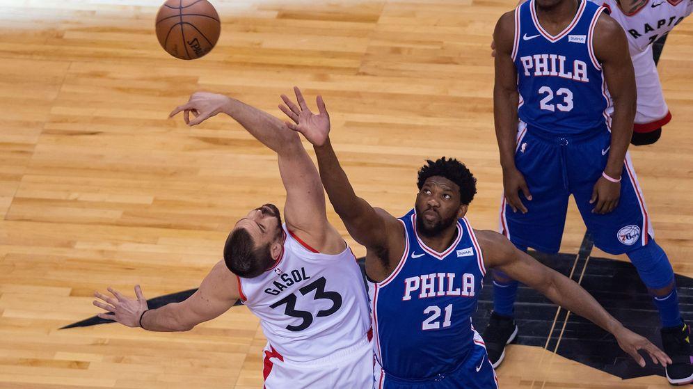 Foto: Marc Gasol y Joel Embiid en el salto inicial del primer partido entre los Raptors y los Sixers. (EFE)