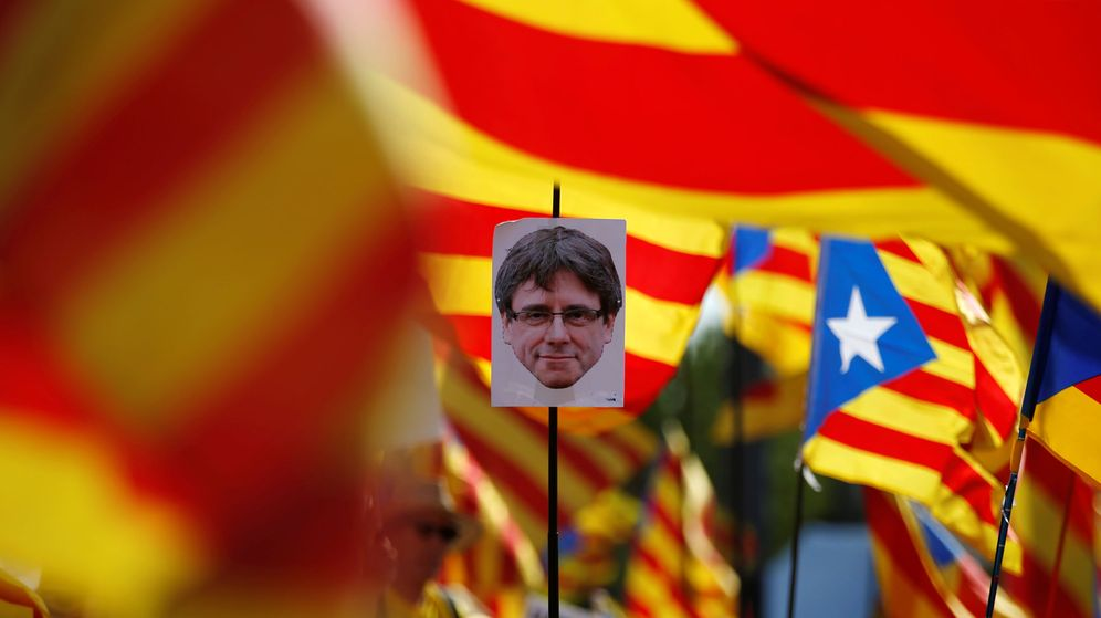 Foto: Un manifestante sostiene un retrato del 'expresident' Carles Puigdemont. (Reuters)