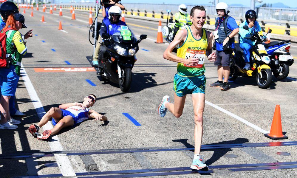 Foto: Callum Hawkins, en el suelo, mientras es adelantado por Michael Shelley. (Reuters)