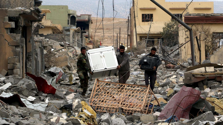 Voluntarios yazidíes transportan objetos recuperables en Sinjar, en noviembre de 2015 (Reuters)
