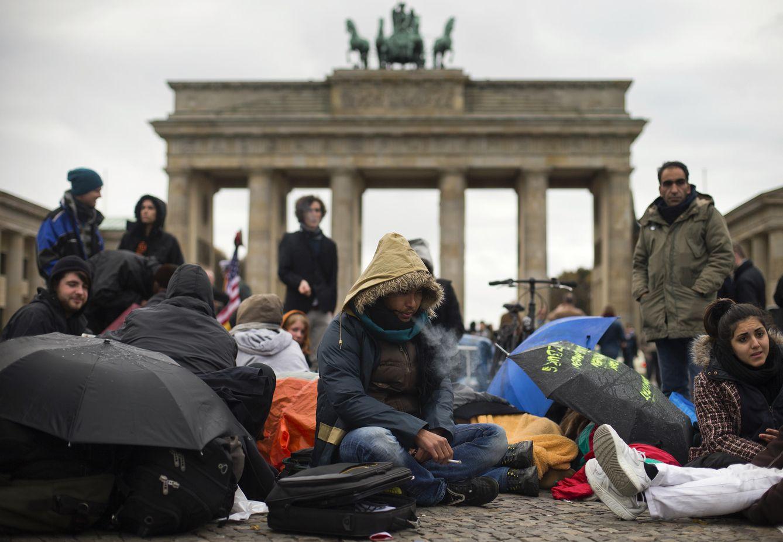 Foto: El refugiado afgano Ali Reza (c) se sienta frente a la Puerta de Brandenburgo, en Berlín, durante una huelga de hambre para evitar ser deportado. (Reuters)