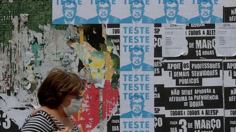 Foto: Una mujer pasa frente a carteles con la imagen del director general de la Organización Mundial de la Salud (OMS), Tedros Adhanom. Foto: Efe