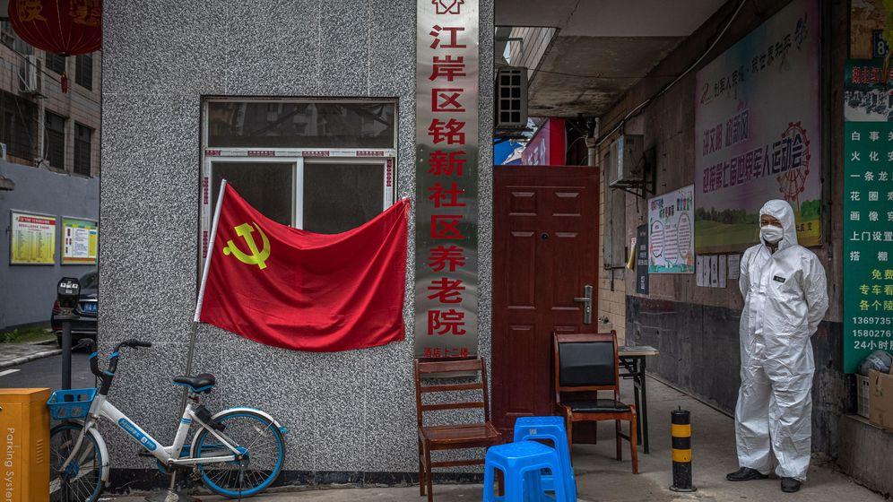 Foto: Un hombre vestido con traje protector, a la entrada de un edificio en Wuhan esta semana. (Reuters)