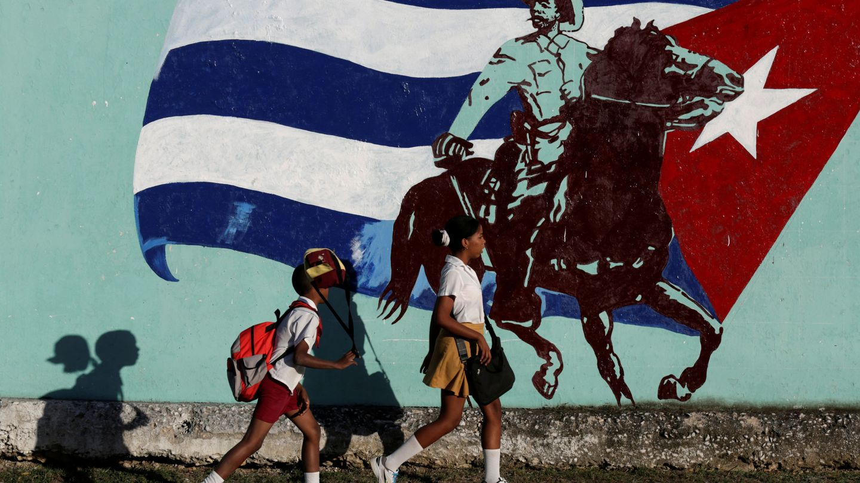 Estudiantes cubanos pasan delante de un mural en La Habana, el 22 de noviembre de 2016 (Reuters)