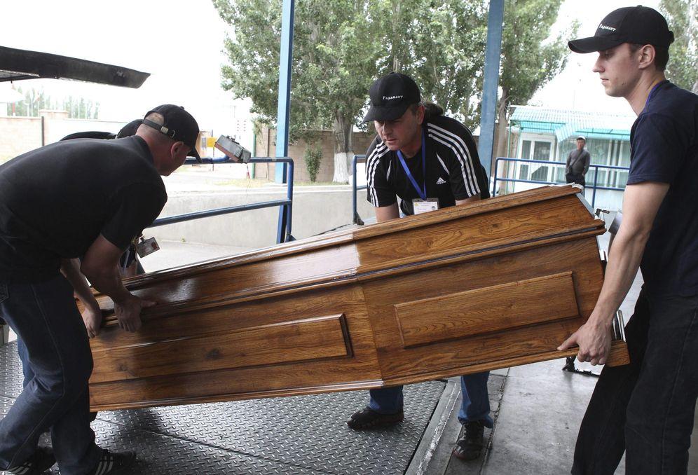 Foto: Empleados de una funeraria, moviendo un ataúd. (EFE)