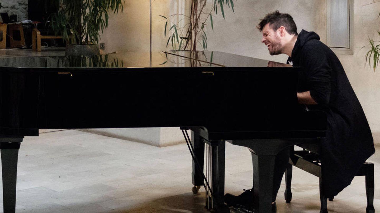 Pablo López toca el piano en un salón de su casa. (Mediaset)