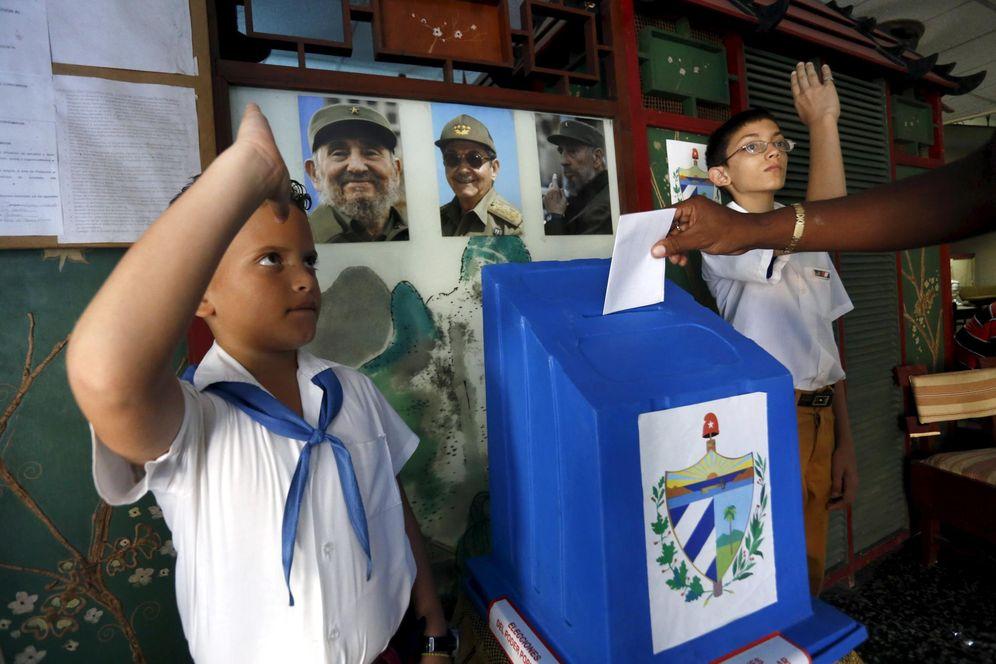 Foto: Dos jóvenes pioneros saludan a un votante en las elecciones municipales en La Habana, el 19 de abril de 2015 (Reuters)