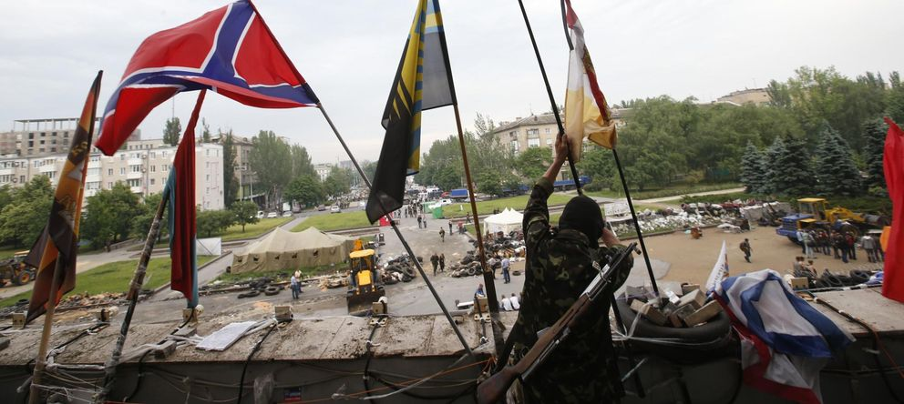 Foto: Un combatiente del Batallón Vostok coloca banderas de milicias separatistas en la sede de gobierno de Donétsk (Reuters).