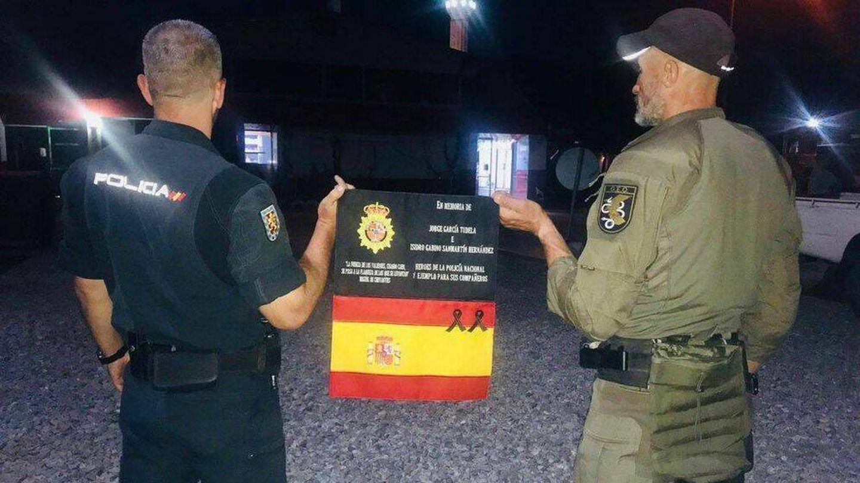 Un agente de la UIP y otro del GEO muestran la bandera en recuerdo de sus compañeros fallecidos desde el aeropuerto en Kabul. (Policía)