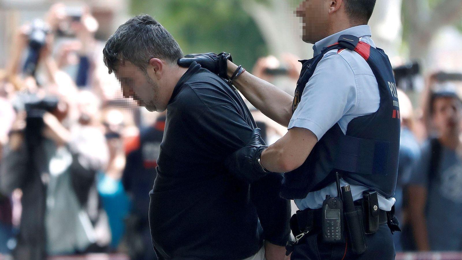 Foto: Varios 'mossos' custodian al detenido. (EFE)