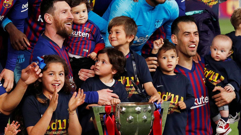 Messi y Busquets celebran el título en el campo. (EFE).