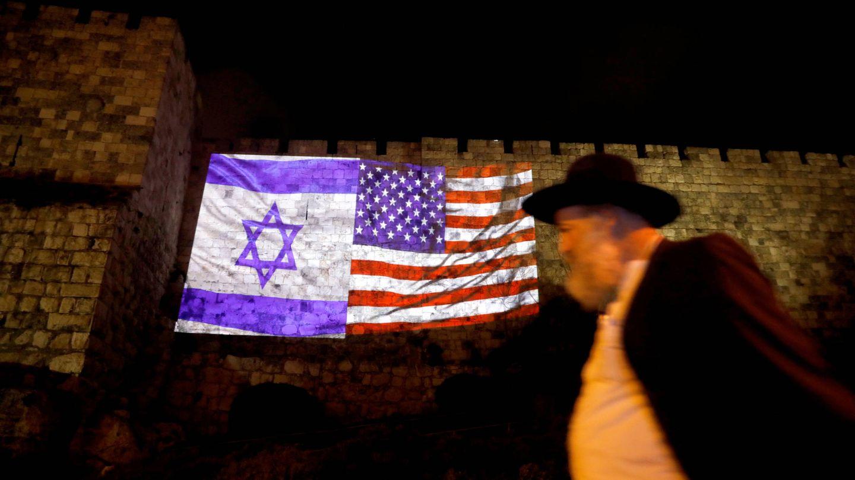 Un hombre camina ante las banderas israelí y estadounidense proyectadas sobre un muro de la Ciudad Vieja de Jerusalén. (Reuters)