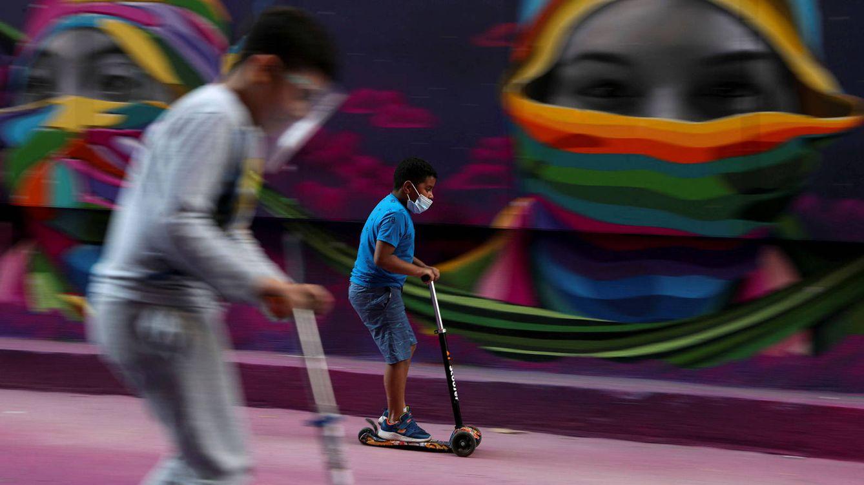 Foto: Dos niños pasan con sus patinetes frente a un mural en Chile. (Reuters)