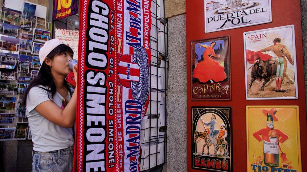Foto: Una turista china, en una tienda de 'souvenirs' del centro de Madrid. (EFE)