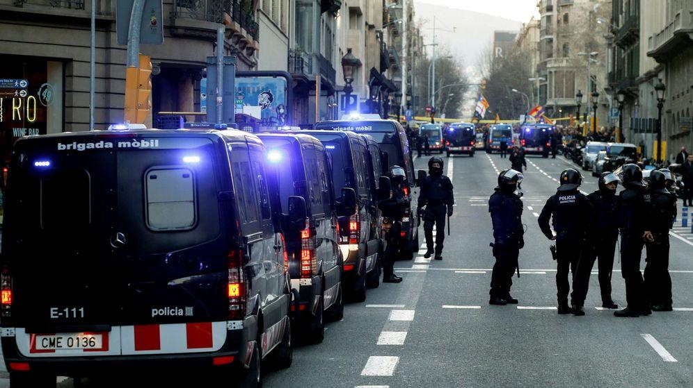 Foto: Miembros de los Mossos d'Esquadra vigilan a manifestantes concentrados en los alrededores del Palau de la Música. (EFE)