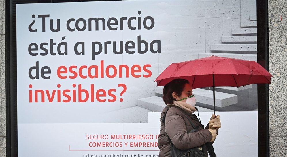 Foto: Una mujer camina junto a una sucursal del Banco Santander, en Alcalá de Henares. (EFE)