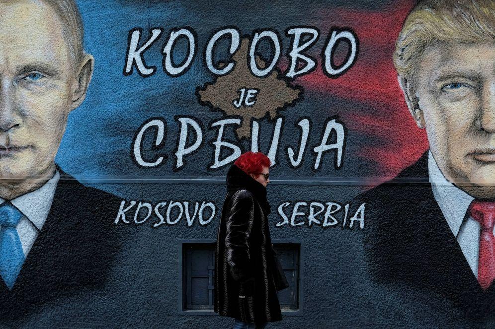 Foto: Una mujer pasa ante un mural con Trump y Putin en Belgrado. La pintada dice: Kosovo es Serbia (Reuters).