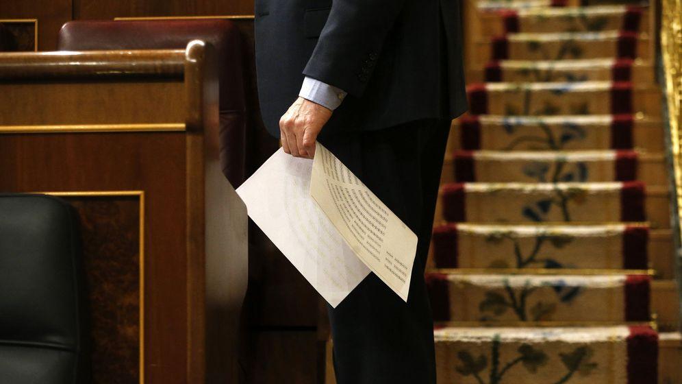 Foto: Un diputado sostiene un papel con la distribución de escaños del hemiciclo. (EFE)