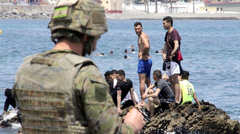 Un soldado observa a varios inmigrantes en la playa fronteriza de El Tarajal, en Ceuta. (EFE)