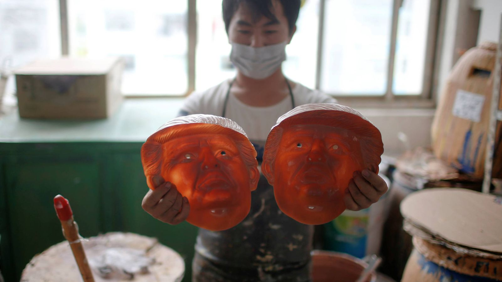 Foto: Un trabajador observa dos caretas de Donald Trump en una fábrica de Jinhua, en la provincia de Zhejiang (Reuters).
