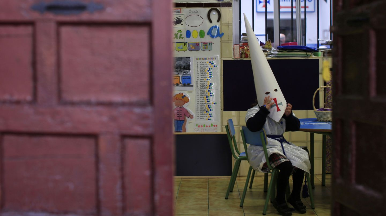 Una niña vestida de penitente en un colegio de Sevilla durante la Semana Santa (Reuters).