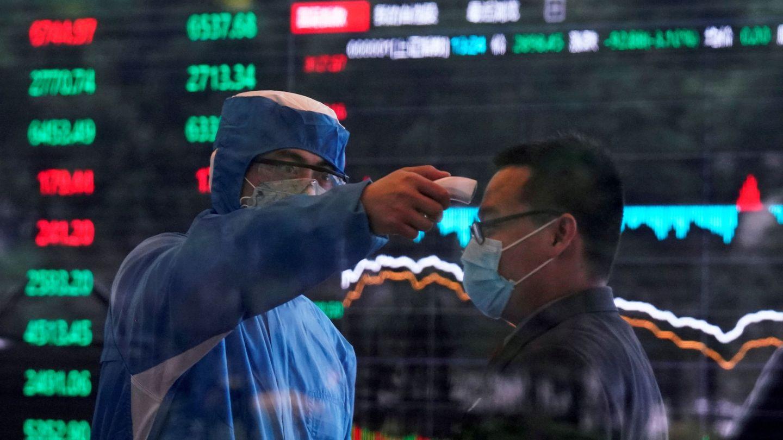 Un médico toma la temperatura a una persona en el interior de la Bolsa de Shanghái. (Reuters)