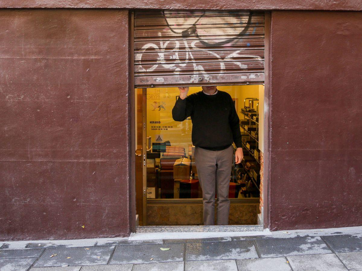 Foto: Un hombre baja el cierre de una tienda. (Europa Press)