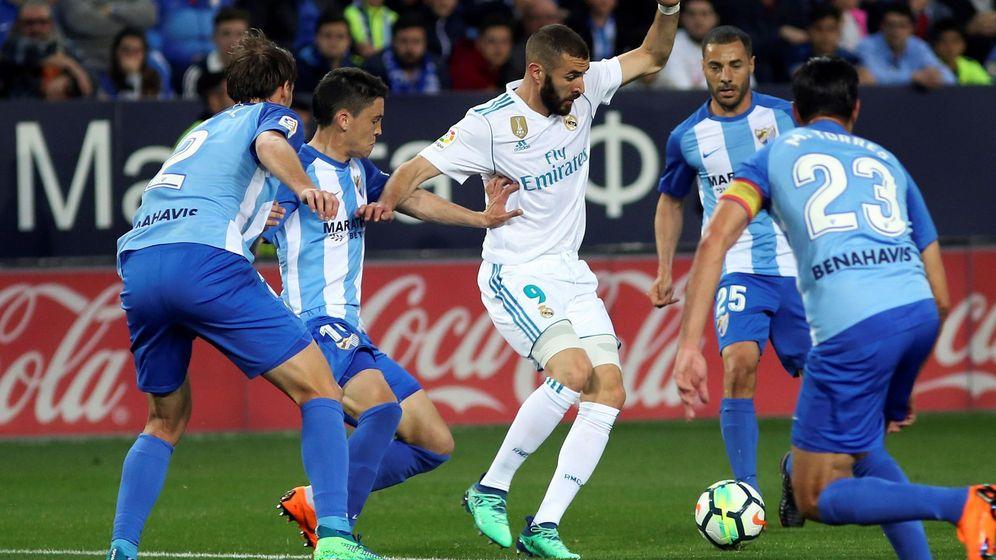 Foto: Benzema, rodeado de jugadores del Málaga, en el partido disputado en La Rosaleda. (EFE)