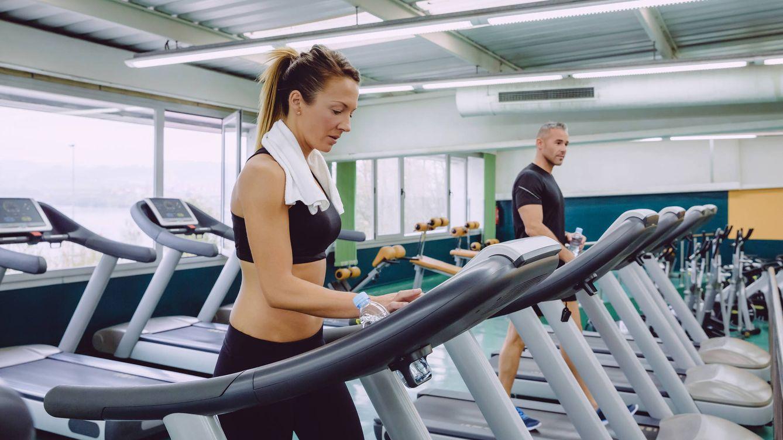 Foto: Una mujer y un hombre en un gimnasio franquiciado. (iStock)