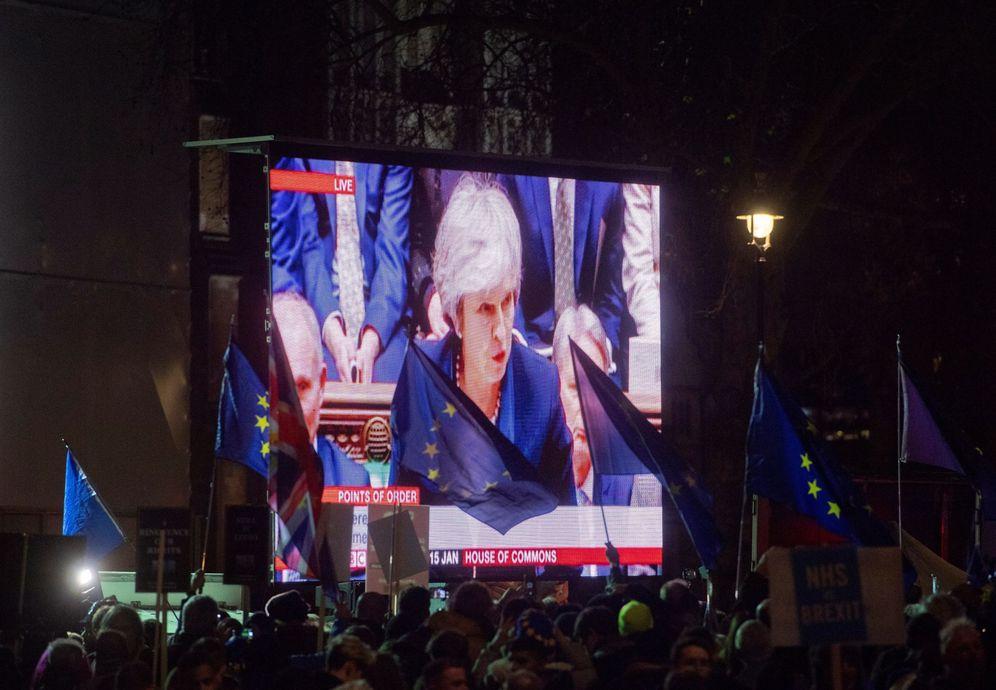Foto: Decenas de personas agitan banderas de la UE mientras miran la intervención de Theresa May en la votación del acuerdo del Brexit, este 15 de enero en Londres. (EFE)