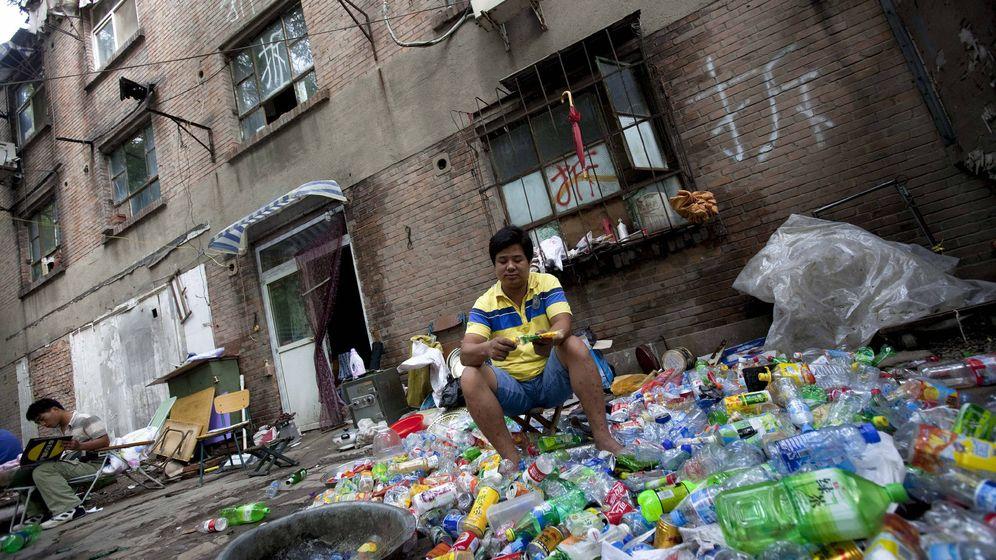 Foto: Un recolector de basura separa materiales reciclables de una pila de desechos frente a un edificio antes de su demolición, en Pekín. (EFE)