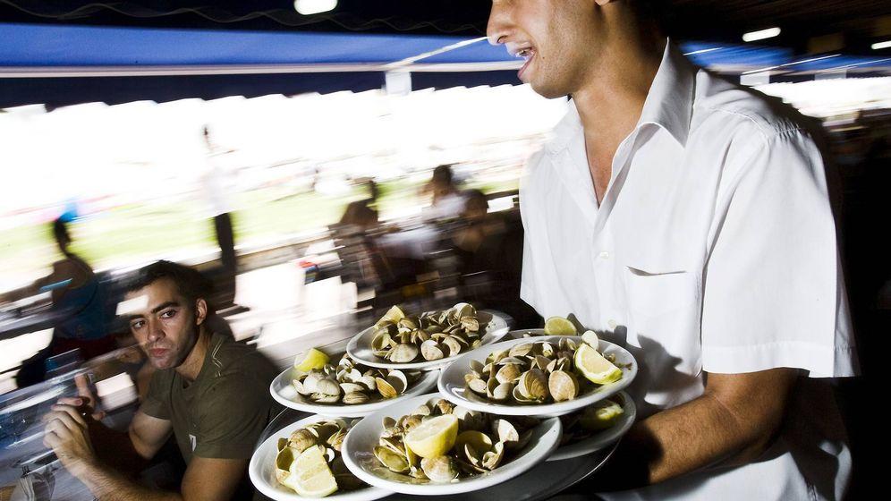Foto: Un camarero porta varios platos en un chiringuito de Málaga. (EFE)