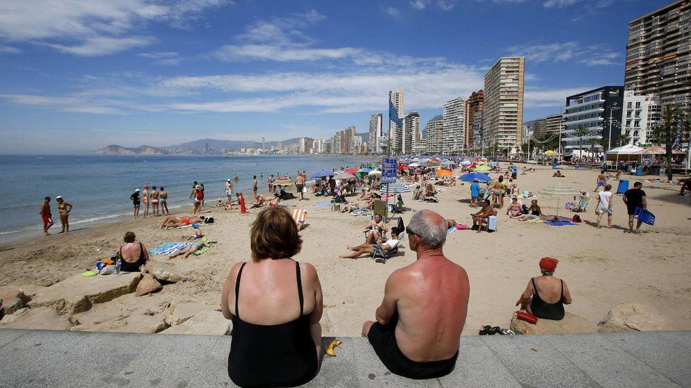 Foto: Dos personas mayores miran sentadas la línea de playa de Benidorm. (EFE)