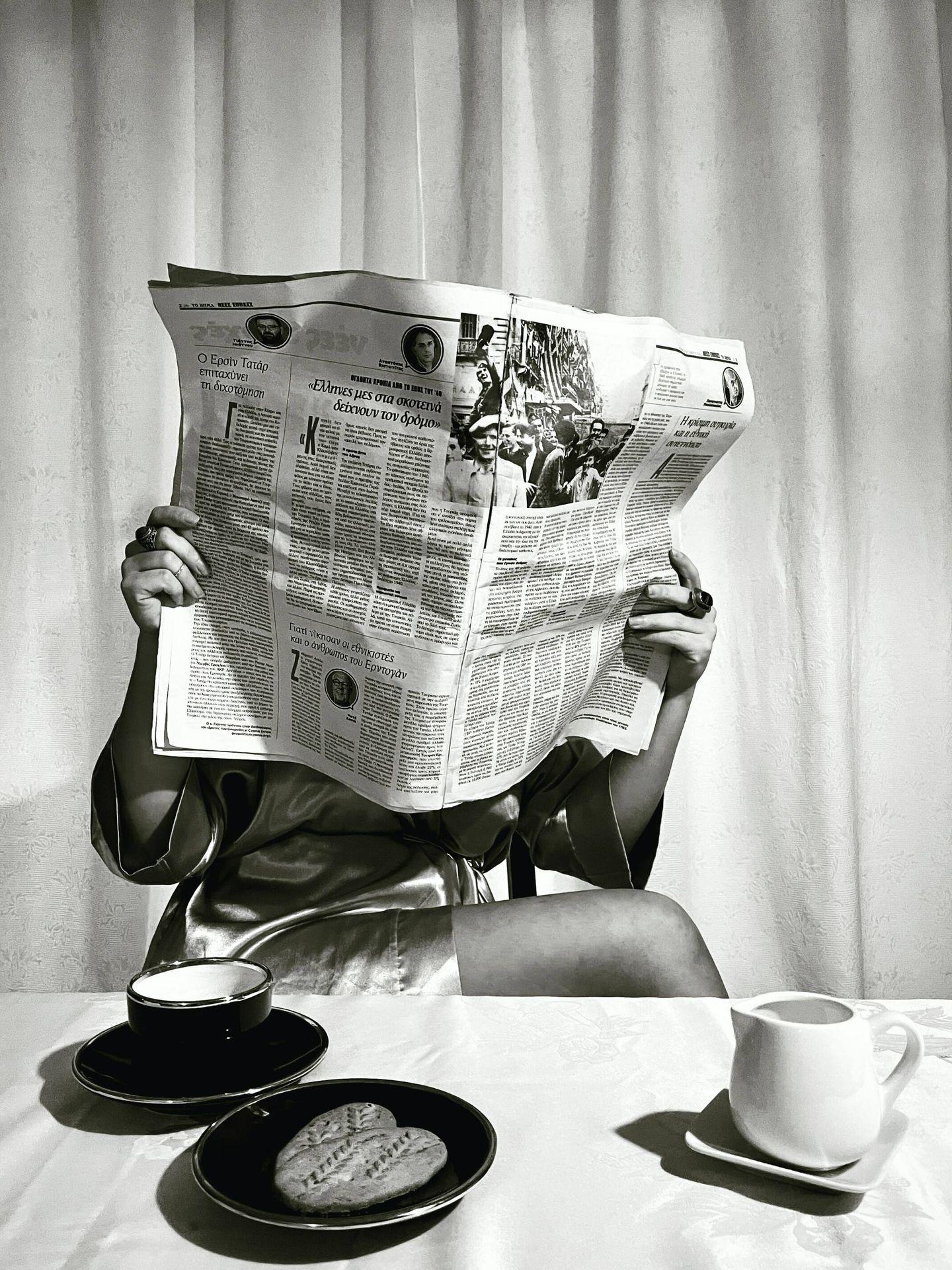 Mujer leyendo un periódico en papel durante el desayuno. (Unsplash)