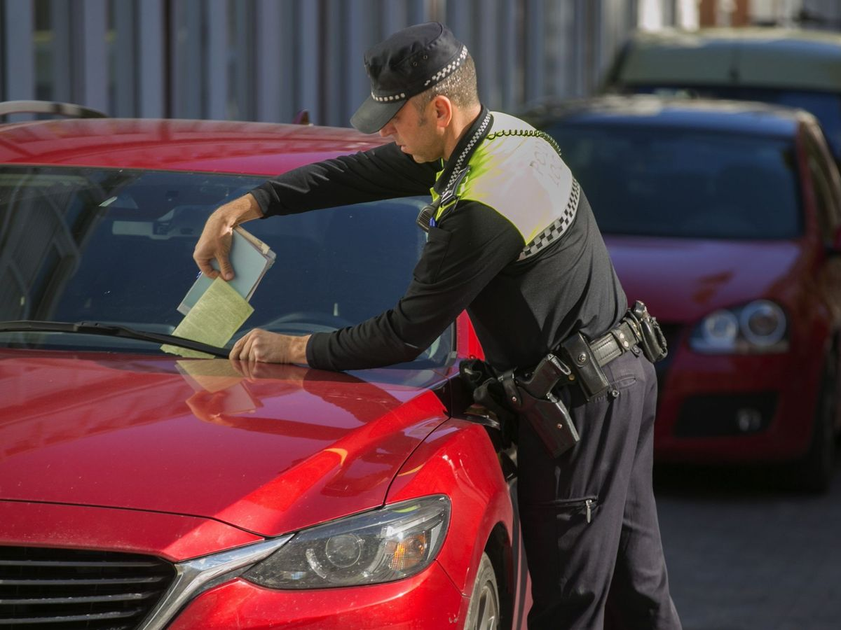 Foto: Un agente de Policía pone una multa en un coche en Vitoria. (EFE)
