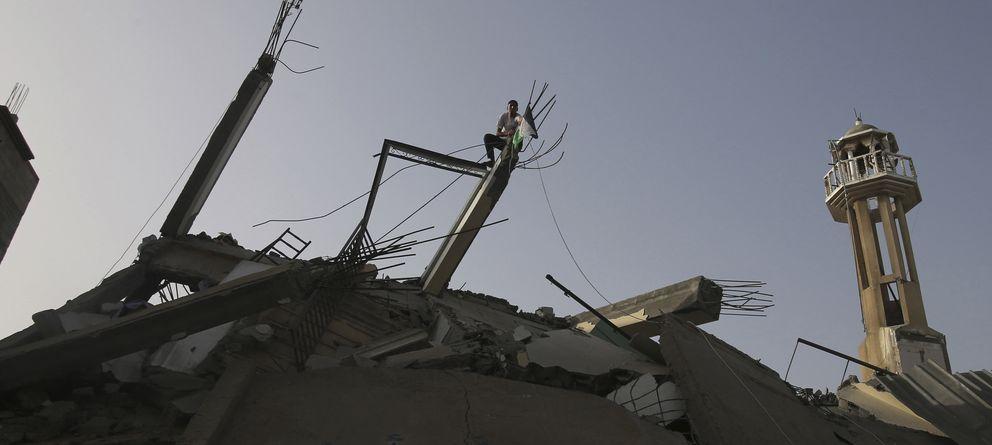 Foto: Un joven coloca una bandera palestina sobre las ruinas de una mezquita en Nuseirat, en el centro de la Franja de Gaza (Reuters).