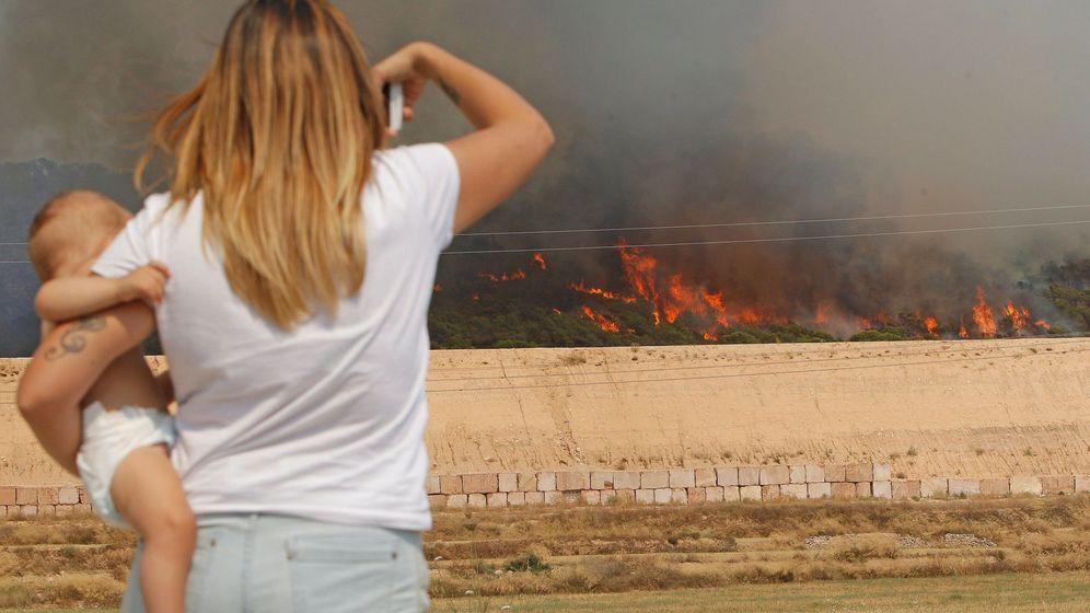 Foto: Una mujer observa el avance de las llamas del incendio forestal que se ha declarado entre las localidades alicantinas de Monóvar y La Romana (EFE)