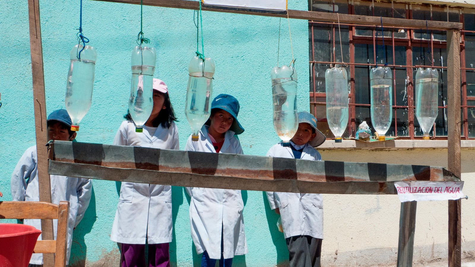 Foto: Niños de la unidad educativa de Achica Arriba (Bolivia) posan con el sistema utilizado para purificar el agua al sol. (Paula Guisado)