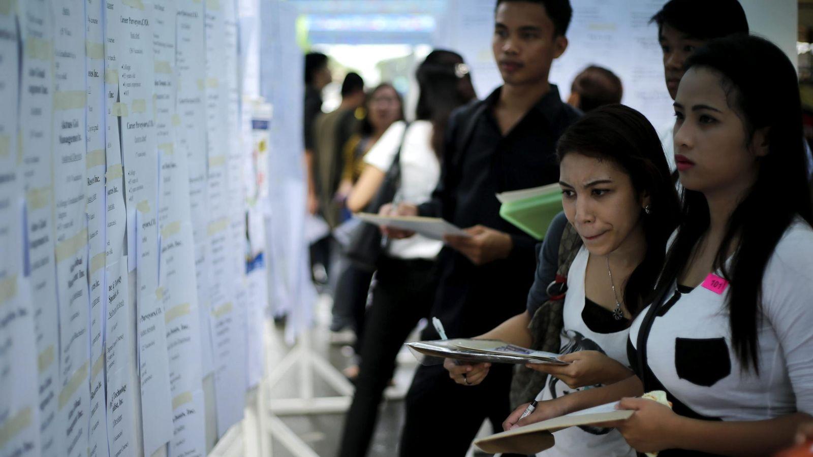 Foto: Un grupo de personas echa un vistazo a varias ofertas de empleo. (EFE)