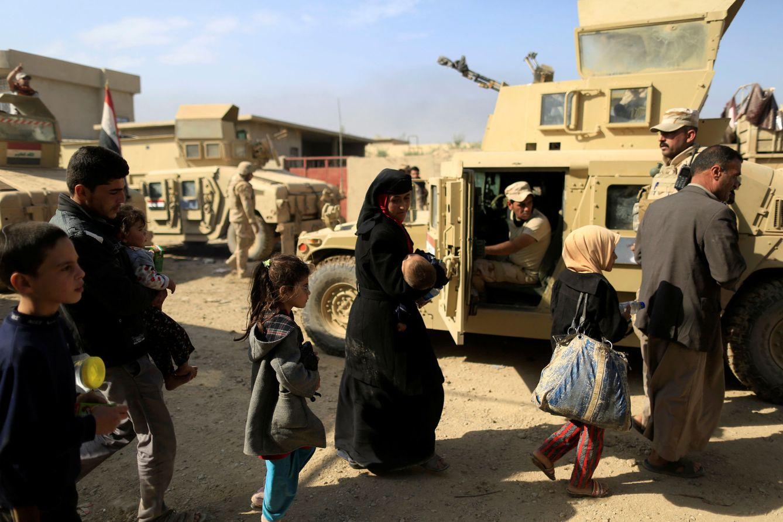 Foto: Iraquíes que huyen de los combates pasan ante un Humvee cerca del frente en Shahrazad, al este de Mosul (Reuters).